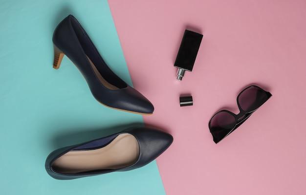 Stilvolle damenaccessoires und schuhe auf rosa blau pastellfarbenem hintergrund leder high heel schuhe flasche parfüm sonnenbrille