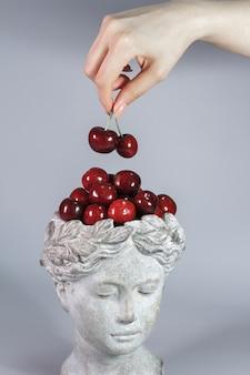 Stilvolle dekoration in form des kopfes der griechischen göttin voller roter reifer kirschen. grauer hintergrund.