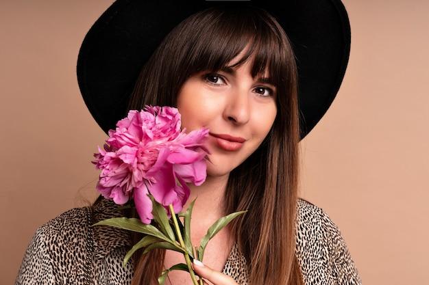 Stilvolle elegante frau, die pfingstrosenblume aufwirft und hält. romantischer glamour-look.