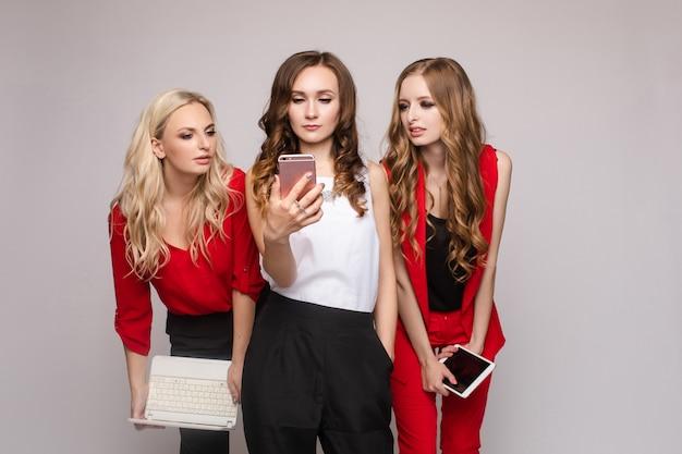 Stilvolle elegante frau im roten anzug mit tablette mit freunden