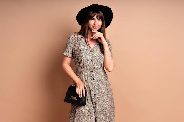 Stilvolle elegante frau mit kleid und hut posiert. elegantes abendoutfit.