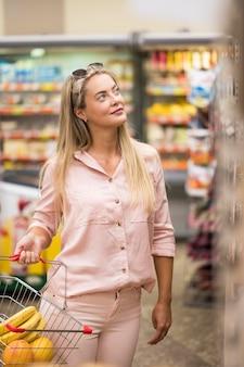 Stilvolle erwachsene frau, die am supermarkt einkauft
