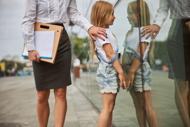 Stilvolle erwachsene frau, die einen ordner mit dokumenten in der hand hält, während sie ihre tochter in der schulter hält