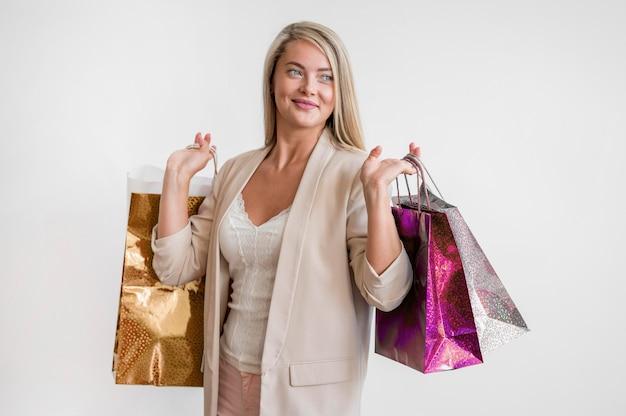 Stilvolle erwachsene frau, die einkaufstaschen trägt