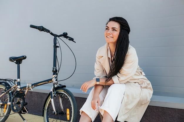 Stilvolle erwachsene frau, die mit umweltfreundlichem fahrrad aufwirft