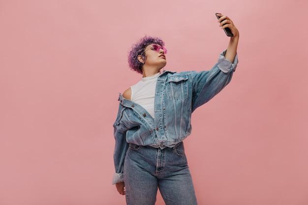 Stilvolle erwachsene frau in leuchtend rosa brille nimmt selfie auf ihrem smartphone. coole frau in übergroßer jeansjacke posiert.