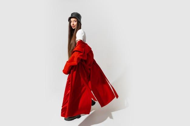 Stilvolle europäische brünette frau in rotem mantel und schwarzem hut posiert auf weißer wand