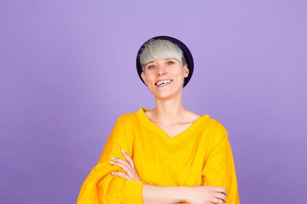 Stilvolle europäische frau auf lila wand. glückliches gesicht, das mit verschränkten armen lächelt, die kamera betrachten