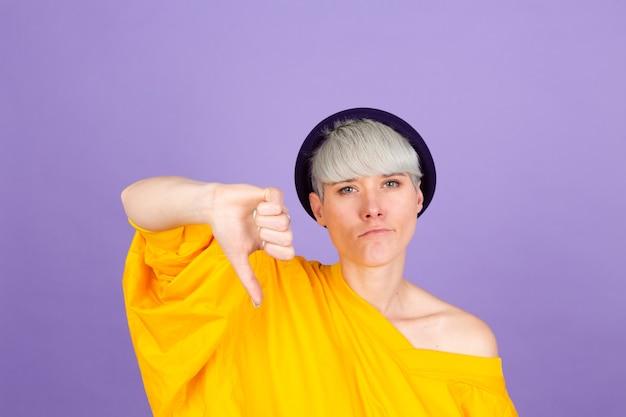 Stilvolle europäische frau auf lila wand. sie sehen unglücklich und wütend aus und zeigen ablehnung und negativ mit daumen nach unten. schlechter ausdruck