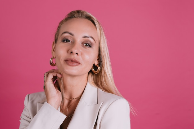 Stilvolle europäische frau in elegantem beige blazer und goldenem schmuck, hübschem make-up und großen lippen, posiert