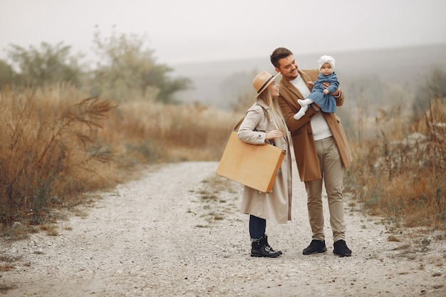 Stilvolle familie, die auf einem herbstfeld geht