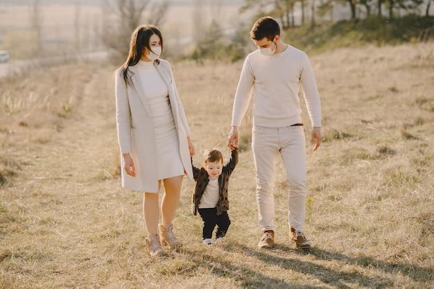 Stilvolle familie, die masken trägt, die auf einem frühlingsfeld gehen