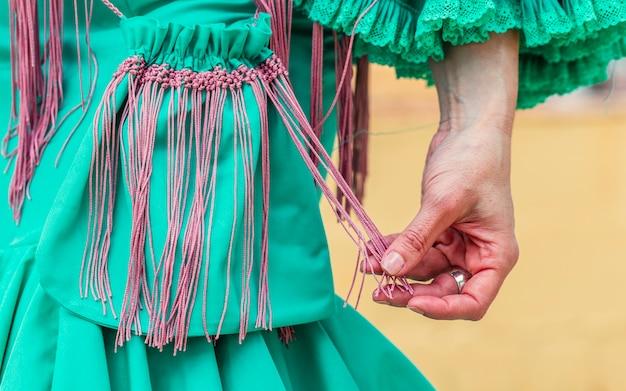 Stilvolle flamencofrau mit grüner weinlesestoffhandtasche mit fransen