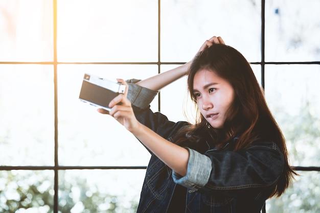 Stilvolle frau asien-schönheit mit einer retro- kamera in der freizeit