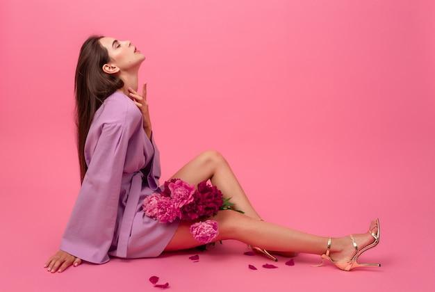Stilvolle frau auf rosa im sommerviolett-mini-trendkleid, das mit pfingstrosenblumenstrauß auf dem boden sitzend aufwirft