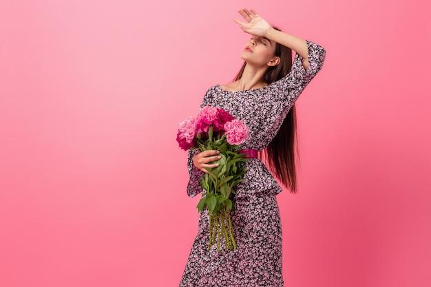 Stilvolle frau auf rosa im trendigen sommerkleid, das mit pfingstrosenblumenstrauß aufwirft