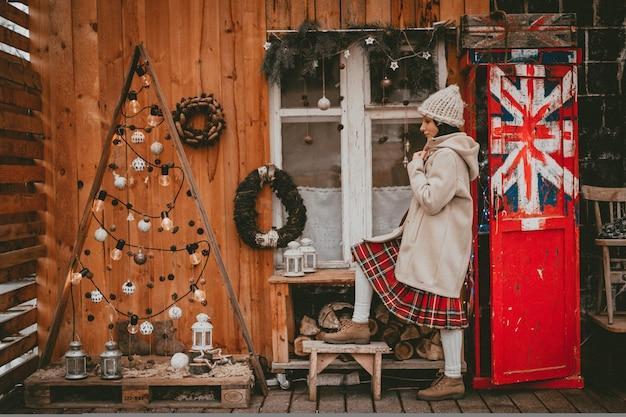 Stilvolle frau dekorierte neujahrsferien terrasse modernen öko rustikalen minimal-stil britische flagge skandinavischen stil handgemachte weihnachten. innendekoration ideen billiges holzfenster, natürliches material