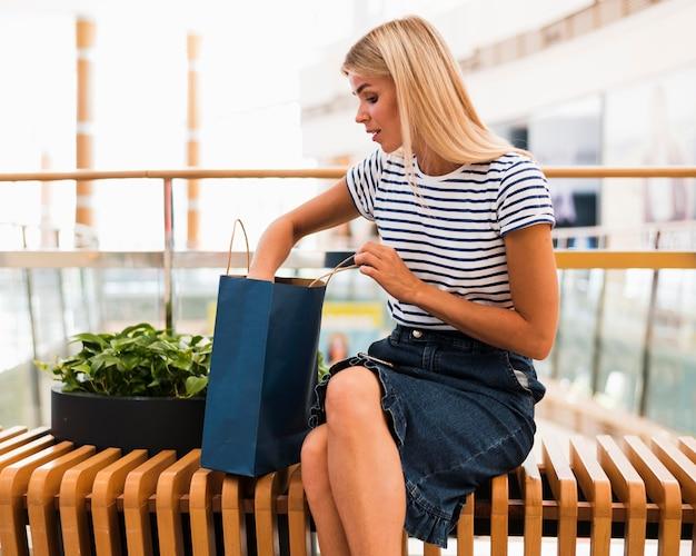 Stilvolle frau der vorderansicht, die einkaufstaschen prüft