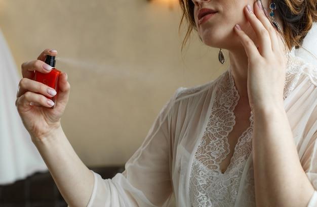 Stilvolle frau des brautspray-parfüms, die ein weißes kleiderspray-angebotparfüm trägt. stilvolle glasflasche parfüm in händen. mädchen mit make-up und eine flasche parfüm.