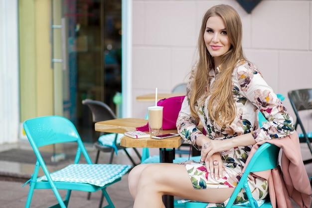 Stilvolle frau des kühlen jungen hipsters, die im modetrend des frühlingsfrühlings des cafés sitzt und kaffee trinkt