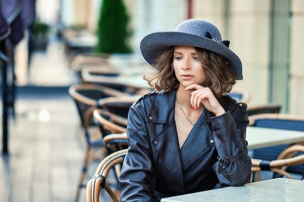 Stilvolle frau, die altmodischen mantel trägt, pause im straßenaußencafé hat