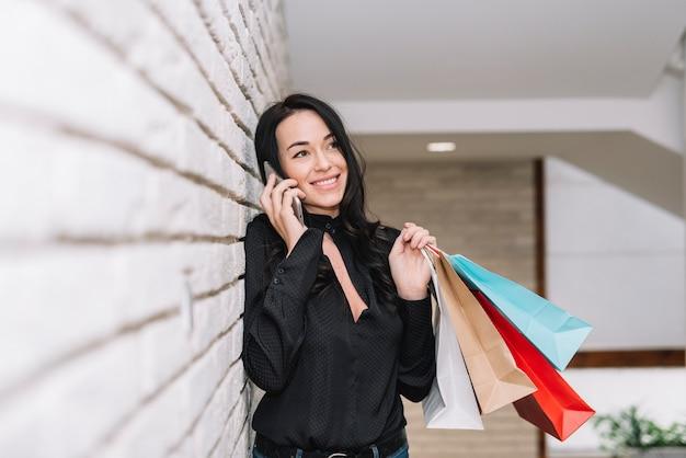 Stilvolle frau, die am telefon kauft und spricht