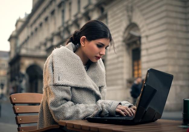 Stilvolle frau, die an einem laptop arbeitet