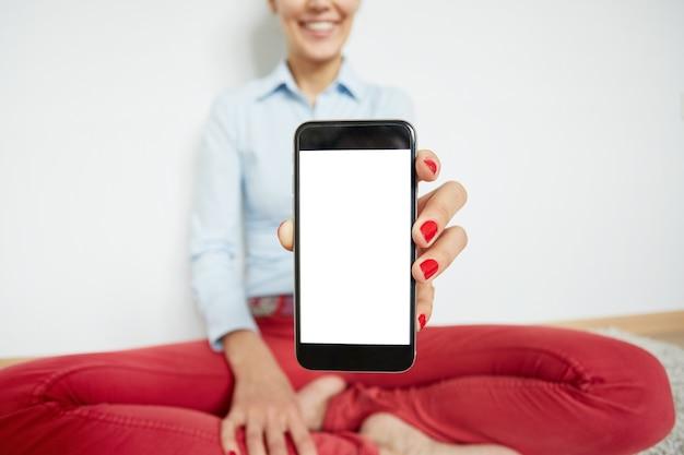 Stilvolle frau, die auf dem boden mit smartphone sitzt