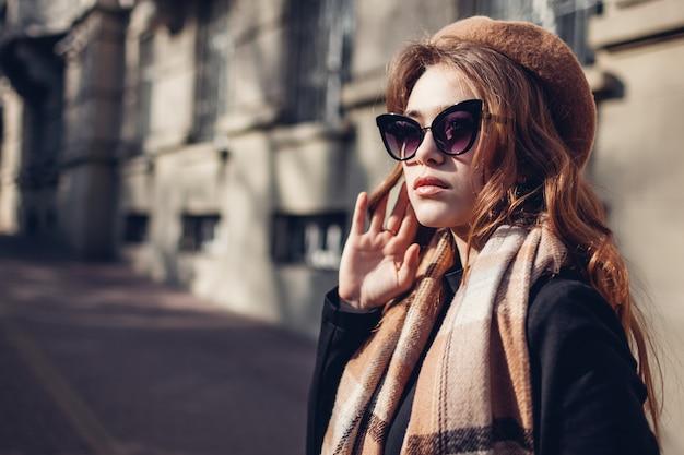 Stilvolle frau, die baskenmütze, sonnenbrille und schal trägt