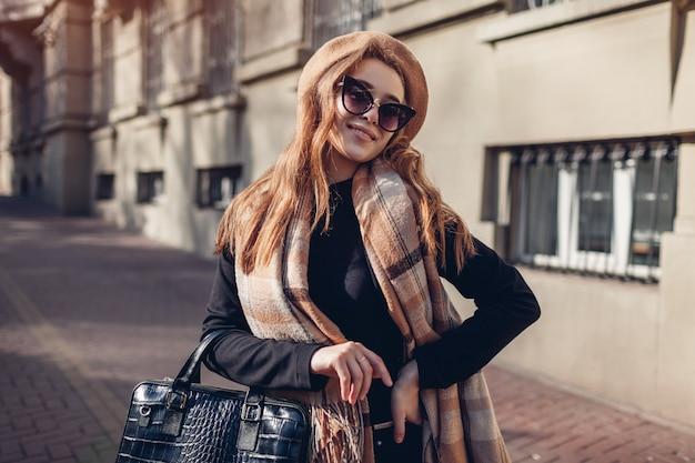 Stilvolle frau, die beige baskenmütze, sonnenbrille und schal hält handtasche trägt