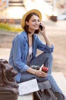 Stilvolle frau, die draußen am telefon spricht