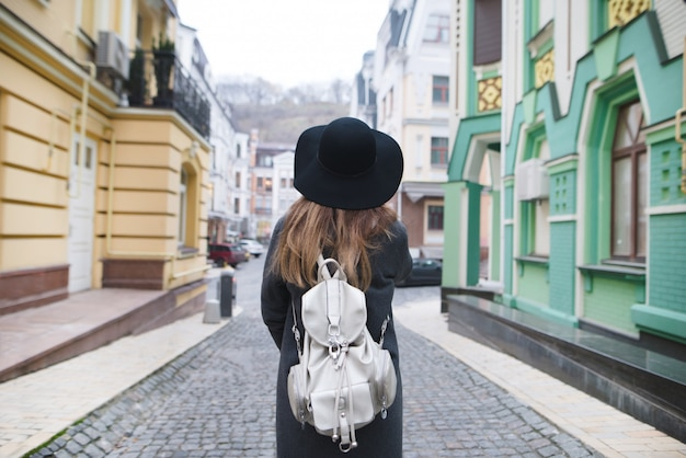 Stilvolle frau, die durch die straßen einer schönen altstadt schlendert.