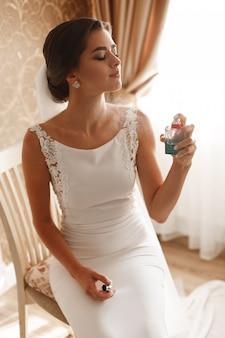 Stilvolle frau, die ein zartes parfüm des weißen kleidersprays trägt