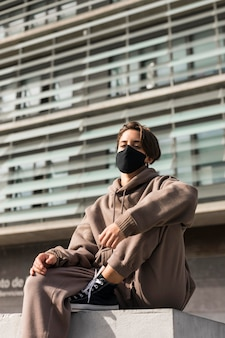 Stilvolle frau, die eine medizinische maske draußen trägt