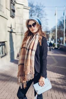 Stilvolle frau, die geldbörse hält und baskenmütze, sonnenbrille und schal im freien trägt