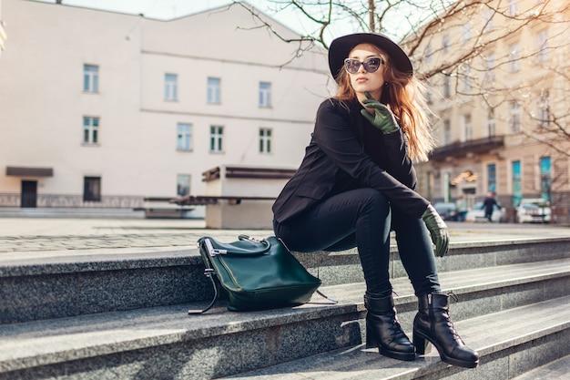 Stilvolle frau, die hut, brille mit grüner handtasche und handschuhe im freien trägt