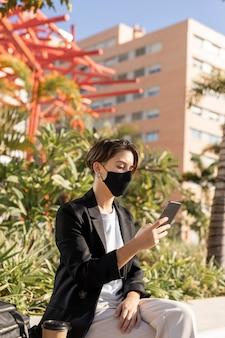 Stilvolle frau, die ihr telefon beim tragen einer medizinischen maske hält