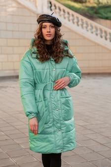 Stilvolle frau, die im winterherbstmodetrend blauen puffermantel und hutmütze in der alten schönen straße aufwirft
