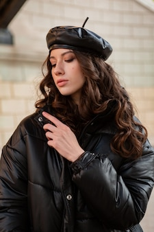 Stilvolle frau, die im winterherbstmodetrend schwarzen puffermantel und lederhutmütze in der alten schönen straße aufwirft