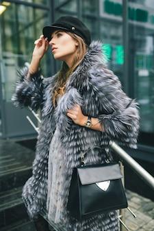 Stilvolle frau, die in der stadt im warmen pelzmantel, wintersaison, kaltes wetter, das tragen der schwarzen kappe, das halten der ledertasche, des straßenmodetrends, des städtischen looks geht