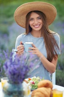 Stilvolle frau, die kaffee im lavendelfeld genießt