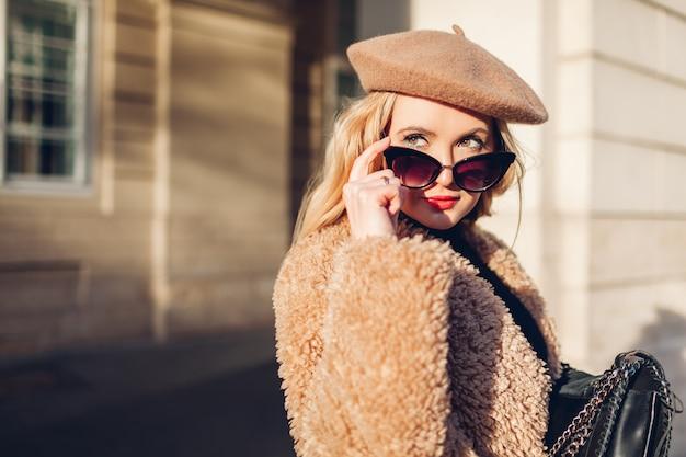 Stilvolle frau, die kleidung, zubehör baskenmütze, sonnenbrille, mantel mit geldbörse trägt