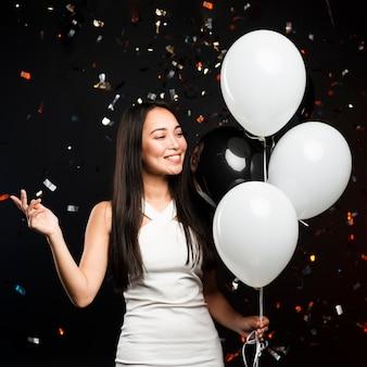 Stilvolle frau, die mit ballonen an der party aufwirft