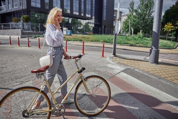 Stilvolle frau, die mit dem fahrrad in der hand auf dem fußgängerüberweg geht, während sie mit dem geschäftspartner am handy telefoniert