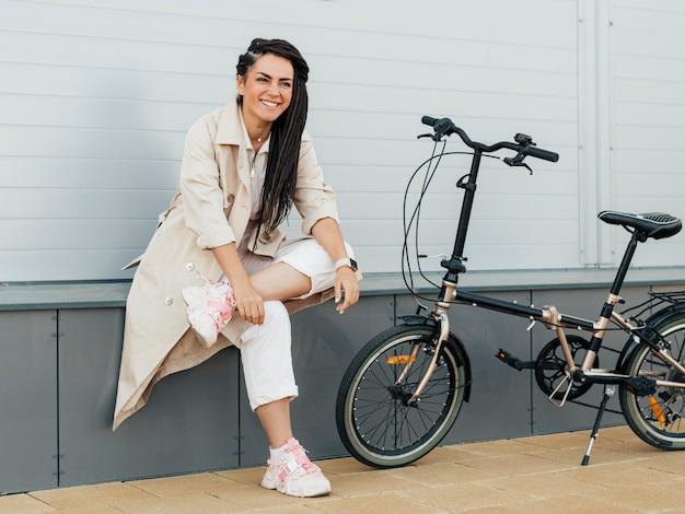 Stilvolle frau, die mit fahrrad aufwirft