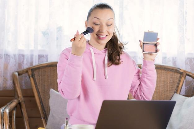 Stilvolle frau, die neue kosmetische produkte und aufnahmeverfahren auf videokamera testet