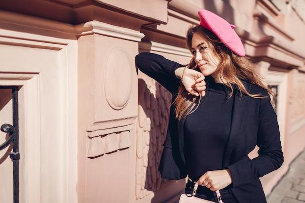 Stilvolle frau, die rosa baskenmütze hält geldbörse im freien trägt
