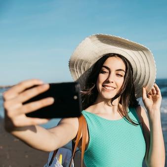 Stilvolle frau, die selfie am strand nimmt