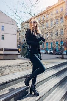 Stilvolle frau, die sonnenbrille trägt und handtasche mit hut hält