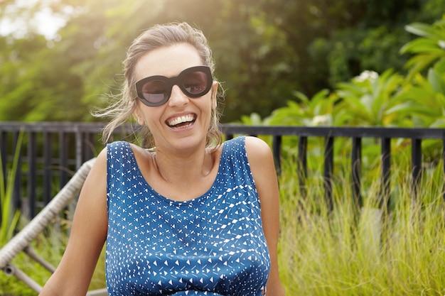 Stilvolle frau, die sonnenbrille und blaues kleid trägt, die draußen gegen grünen wald entspannen, glücklichen und freudigen blick haben.